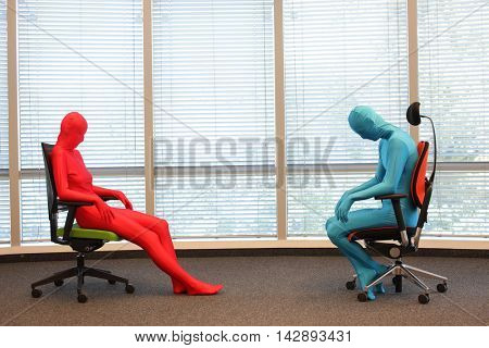 anonymous couple in full body elastic suits sitting on armchairs