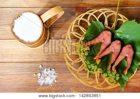 Beer snack salty red fish with foamy beer in mug pint on a wooden table background