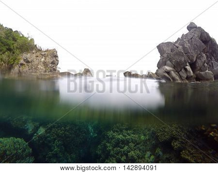 Cloudy sky and sea split by waterline at Apo island Philippines. Underwater view with coral reef and marine life. Rocks and land with forest above water line. Real waterline photo Background image