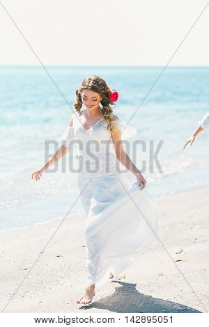 Passionate newly-weds are having fun and running at the seashore.