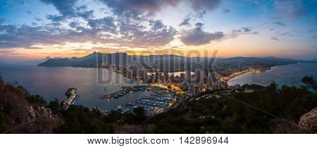Aerial view of Calpe, Costa Blanca at sunset. Popular summer resort in Spain with mediterranean sea and Las Salinas lake, mountains at the background. Illumination and city lights, skyscrapers