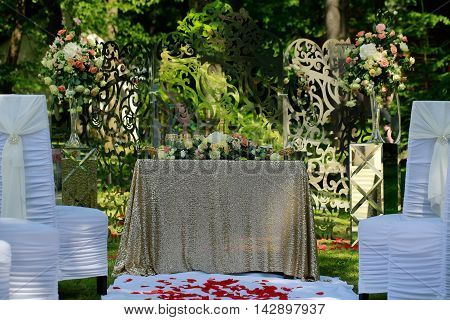 Wedding table covered with golden tablecloth flowers for formal marriage ceremony decorated with beautiful bouquets and chairs on natural background outdoor