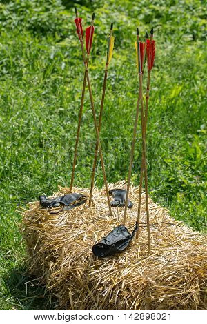 Six arrows with red with yellow feathers in and black leather arm bands laying on hay stack in summer on green grass background outdoor