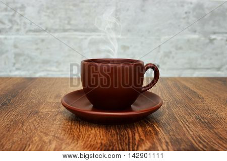 Brown coffee cup with a saucer and aromatic smoke on the wooden table close-up.