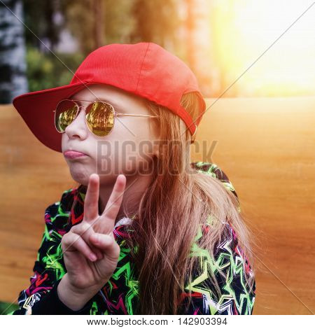 Beautiful girl in sunglasses and a cap showing victory gesture outdoors.