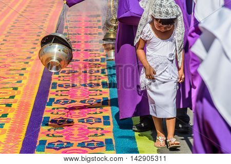 Antigua Guatemala - March 25 2016: Locals reenact biblical scenes walking over handmade dyed sawdust carpets & burning incense on Good Friday in colonial town with most famous Holy Week celebrations in Latin America.