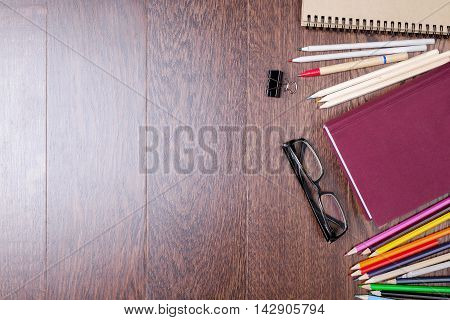 Top view of dark wooden office desktop with glasses closed book colorful pencils pen spiral notepad and other stationery items. Close up Mock up