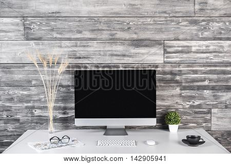 Creative designer workplace with blank pc monitor keyboard mouse coffee cup decorative plants paperwork and glasses on wooden plank wall background. Mock up