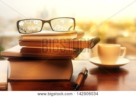 Spectacles with business icons on desktop with spiral notepads coffee cup pen and book stack. Closeup