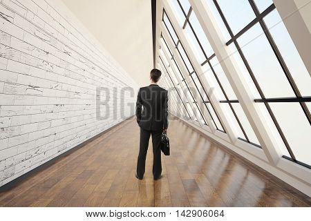 Businessman walking in clean corridor interior with dark wooden floor light wall concrete ceiling and panoramic window. 3D Rendering