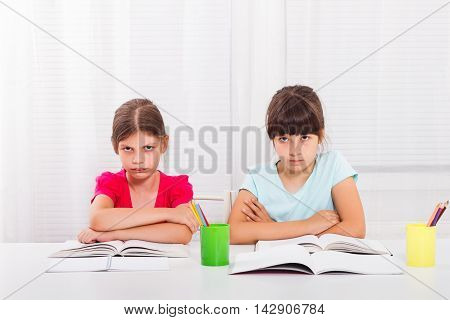 Angry little girls must stay at home and do their homework,but they would rather play outside.