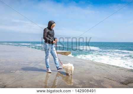 Happy woman with a doggie of in the early spring near the sea