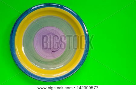 Dinner plate blue yellow green and purple on a neon green background