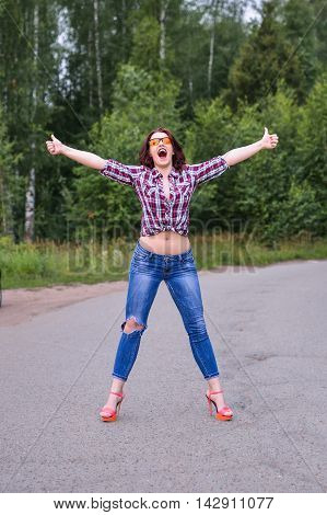 Young woman persistently hitchhiking gesture at countryside.