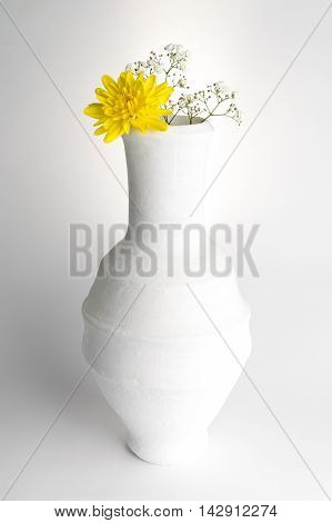 Still life composition of white pottery vase yellow flower and small white flowers on white background