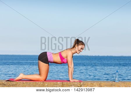 Woman Doing Sports Exercises Outdoors By Seaside