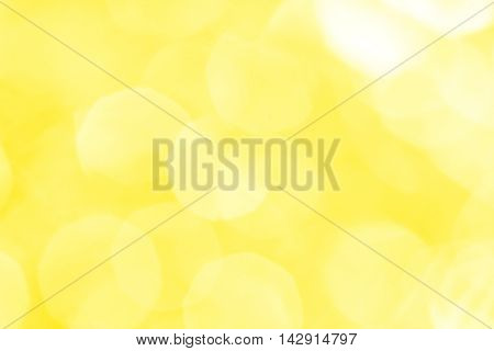 Abstract yellow background with white spots and patches of light