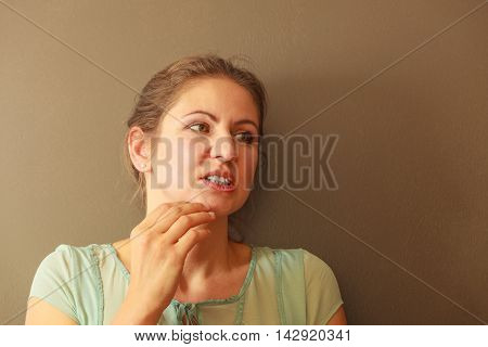 Aches and pains concept. Woman having bad ache and pain. Female feel tooth ache touching her mouth from outside by hand palm.