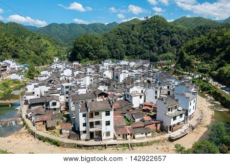 08/11/2016 WuyuanChina - Circular shaped old town surrounded by an empty riverbed in the wuyuan mountain area on a sunny day with cloudy blue sky