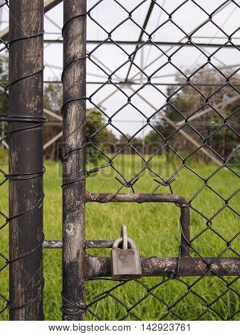 Padlock on a wire security fence door in front of a high voltage power pole Melbourne 2016