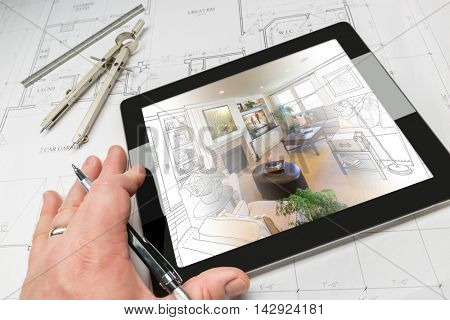 Hand of Architect on Computer Tablet Showing Living Room Illustration Photo Combination Over House Plans, Compass and Ruler.
