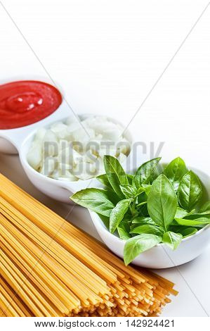 Basil sliced onions and tomato paste in white bowl with raw spaghetti on white background. copy space