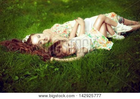 beautiful girl with long hair lying next to his pregnant mother in the summer on the green grass. Stay for the weekend