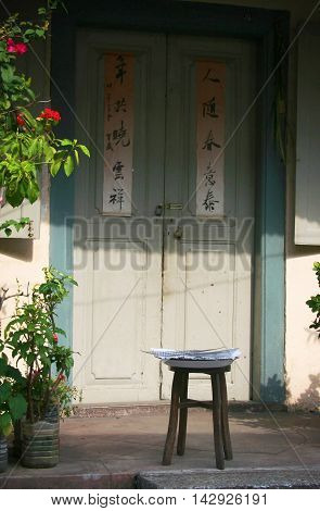 A stool in front of a Chinese door in Malacca, Malaysia