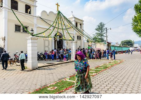 Parramos Guatemala - May 29 2016: Traditionally dressed Mayan woman walks past church overflowing during Corpus Christi mass.
