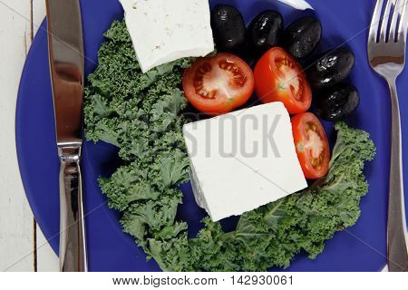 white goat feta cheese with black olives and tomatoes on blue plate over wooden table
