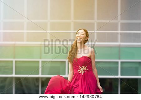 Happy and smiling cute Asian woman walking in red evening dress.