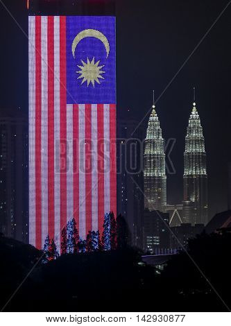 KUALA LUMPUR MALAYSIA - APRIL 04 2013: Giant Malaysia flag 'Jalur Gemilang' display using led light at Dato Onn Tower with Petronas Twin Towers at the background.