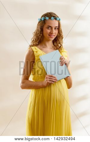 Pregnant woman wit copy space book in yellow dress, studio