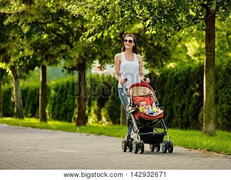 beautiful young woman pushing baby carriage in the park