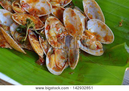 stir fried clams with roasted chili paste on fresh banana leaf