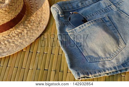 woven hat and sunglasses in blue jean pocket under sunlight