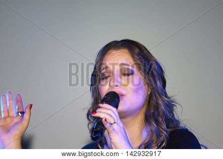 BRONX NEW YORK - SEPTEMBER 9: Female singer Christine D' Clario performs during a Christian concert at a local high school for Realizing Possibilities ministry. Taken September 9 2012 in New York.