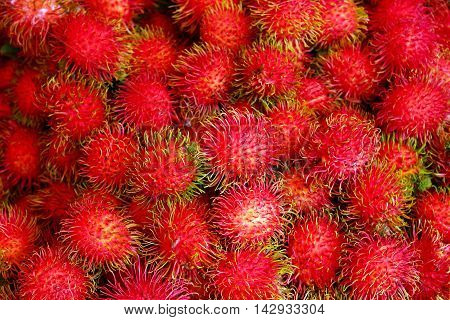 Close up of a pile of red rambutan, the tropical fruit