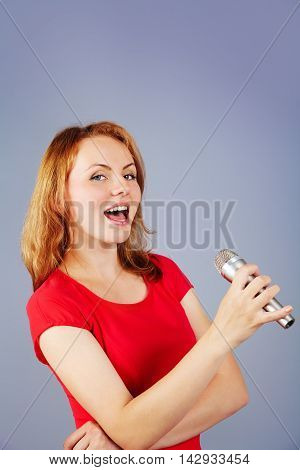 woman is singing song with a microphone.  isolated on gray studio background