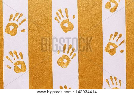 Hand prints on yellow and pink wall