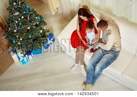 young family celebrating Christmas at home. father, mother and child sitting on the couch talking by mobile phone with his grandparents. New Year and xmas people
