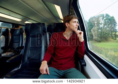 handsome man riding on a train and looking out the window. traveler on the road