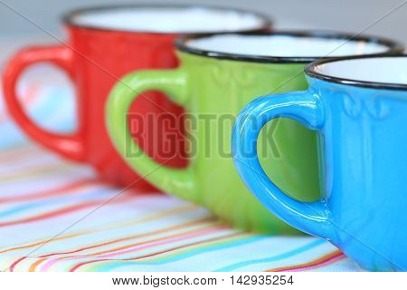 Colorful Row of Cappuccino Cups on a Striped Table Cloth.