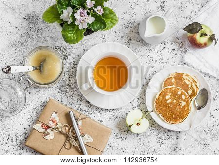 Tea pancake apple sauce homemade gift in kraft paper flower violet on a light background. Romantic breakfast table. Vintage style top view