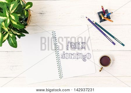 Cup of tea in morning and text in Notepad: Felize Domingo. Happy Sunday In Spanish. Flat lay