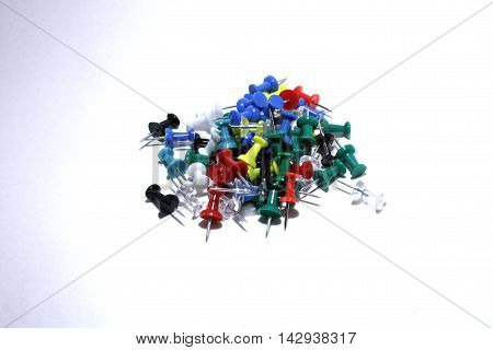 Colored thumbtacks rolled in bulk on a white background