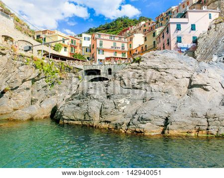 Manarola, Cinque Terre, Italy - September 09, 2015: Colorful traditional houses on a rock over Mediterranean sea at Manarola, Cinque Terre, Italy