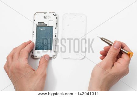 Smartphone disassembling with special tools. Phone repair service, male hand removing plastic case from communication device, white background