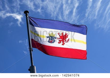 flag of Mecklenburg-Vorpommern blowing in the wind against the blue sky a symbol of the federated state on the Baltic Sea in northeastern Germany with the bull's head for Mecklenburg and the grasping of Vorpommern
