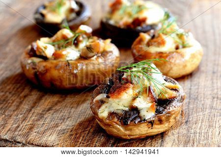 Mushroom caps stuffed with cheese and meat, baked in oven and garnished with a sprig of dill. Mushroom appetizer on wooden board. Closeup